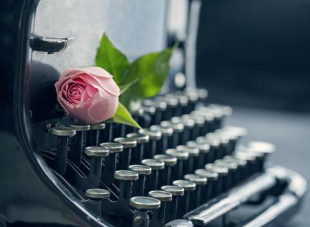 핑크 로맨틱 로즈와 함께 오래 된 골동품 검은 빈티지 타자기