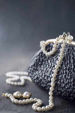 Old elegant vintage handbag from the 1950s with luxury pearls on black background for copy space