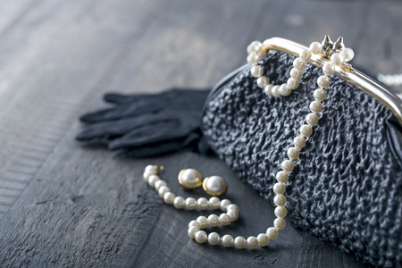 Old elegant vintage handbag from the 1950s with luxury pearls and earrings on black background for copy space