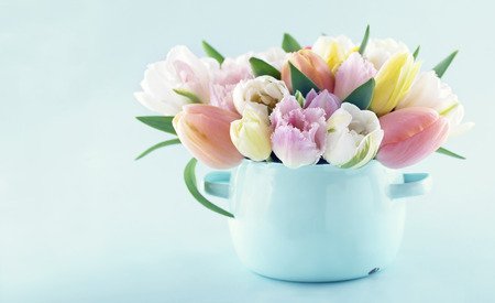 コピー スペースを持つ明るい青のパステル背景にヴィンテージ花瓶にばねのチューリップの花束