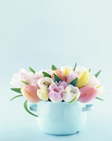 Bouquet of spring tulips in a vintage vase on light blue pastel background with copy space Stockfoto