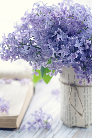purple lilac: Bouquet of purple lilac spring flowers with an open book and vintage hazy editing Stock Photo