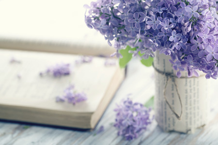 mazzo di fiori: Bouquet di fiori viola lilla di primavera con un libro aperto e vintage editing nebbioso Archivio Fotografico