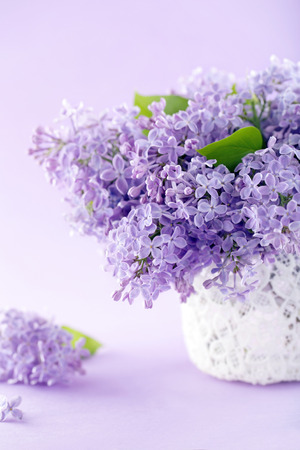 White vase with a bouquet of purple lilac spring flowers