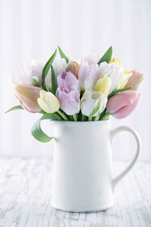 tulips in vase: White vase with colorful tulips on wooden background with vintage hazy editing