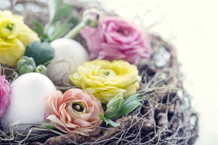 Paaseieren en bloemen in het nest van een rustieke vogel met wazige vintage editing Stockfoto