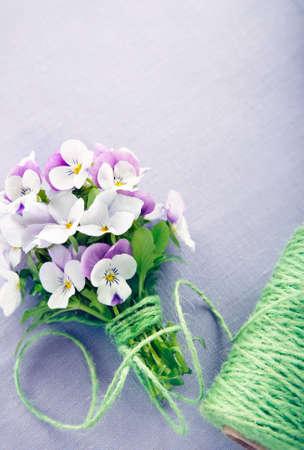 Boeket van paarse viooltjes op lila linnen achtergrond