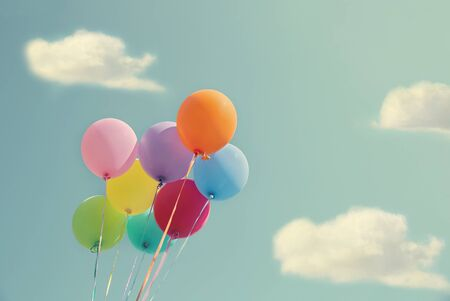 colourful sky: Bunch of colorful balloons on a blue sky with vintage editing Stock Photo