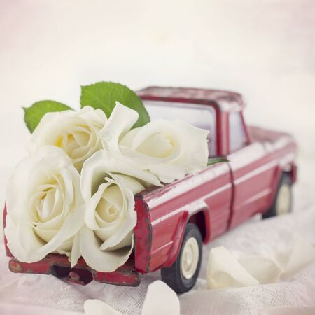 Rode stuk speelgoed vrachtwagen met witte rozen en romantische bruiloft achtergrond