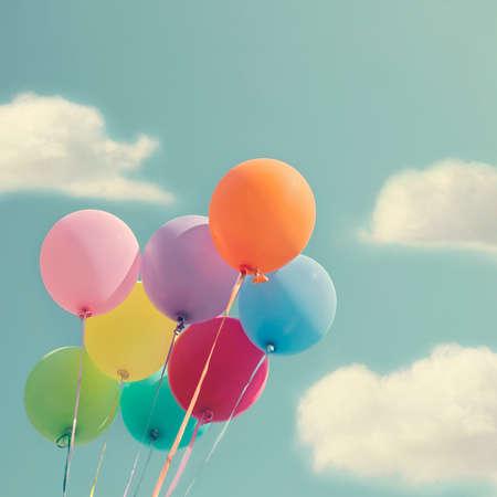 Bos van kleurrijke ballonnen op een blauwe hemel met vintage editing