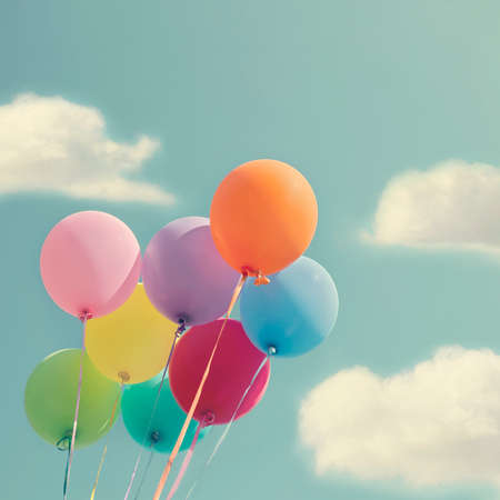 Bunch of colorful balloons on a blue sky with vintage editing Banco de Imagens