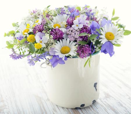 Ramo de flores silvestres en el fondo de cosecha de madera blanca