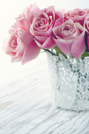 Pink roses in a white lace vase on wooden vintage background