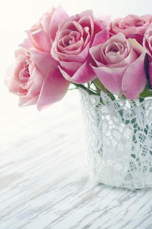 Roze rozen in een witte kant vaas op houten uitstekende achtergrond