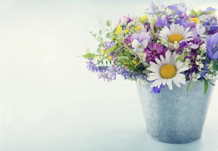 blue light background: Wild flower bouquet on light blue vintage background