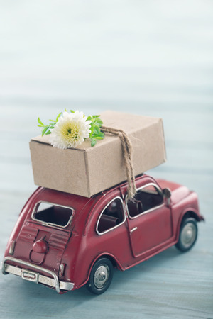 Rode stuk speelgoed auto gepakt met een bruine bewegende doos en lichtblauwe vintage achtergrond