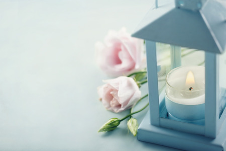 Small candle in a blue lantern with pink flowers - condolences concept 版權商用圖片 - 64798602