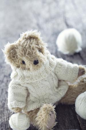 Leuke teddybeer met een wollen trui en ballen van draad op vintage houten achtergrond