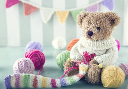 knitting: Teddy bear in a woolen sweater knitting a striped scarf with colorful balls of yarn