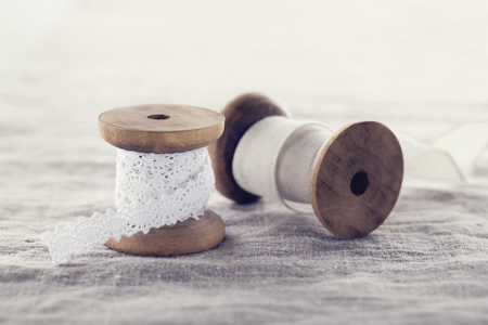 Wooden ribbon spools with beige and white lace on linen background with hazy vintage editing
