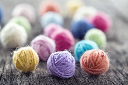 Colorful yarn balls on pink wooden vintage background