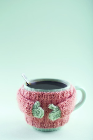 Cup of black coffee with a handmade knitted sweater on green background with copy space