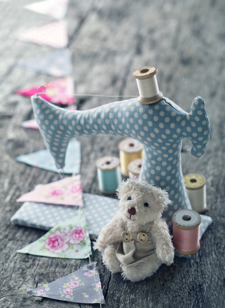 Toy sewing machine with colorful bunting and a small teddy bear with vintage hazy editing on wooden background