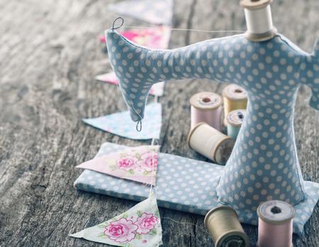 Toy naaimachine met kleurrijke gors en een kleine teddybeer met vintage wazige editing op houten achtergrond