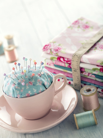 measuring cup: Green handmade floral pincushion in a pink cup with old spools of thread, sewing concept background
