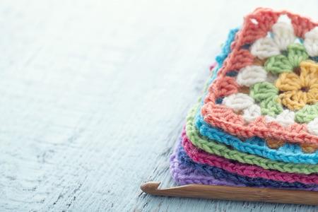 Pile of colorful crochet granny squares on light blue wooden vintage background