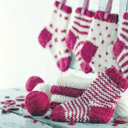 Small Christmas socks and balls of wool yarn Banco de Imagens