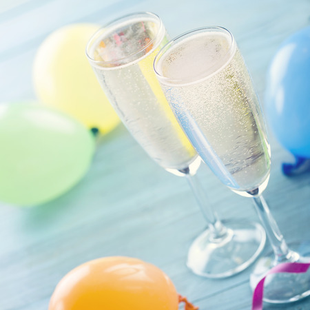 Two glasses of champagne and colorful balloons on blue wooden background - a party concept