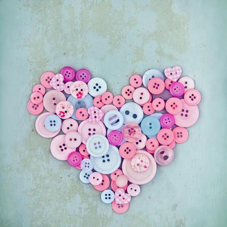 Heart symbol of pink buttons on light blue wooden vintage background