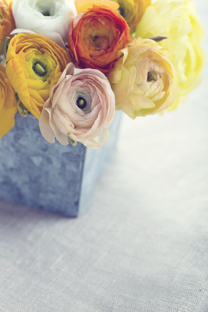 Bouquet of orange and yellow color ranunculus flowers in a metal tin cup on grey background with vintage hazy editing Banco de Imagens