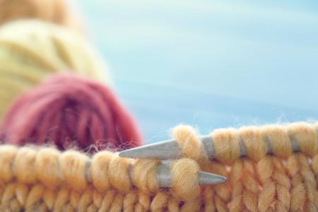 Closeup of knitting with soft orange woolen thread