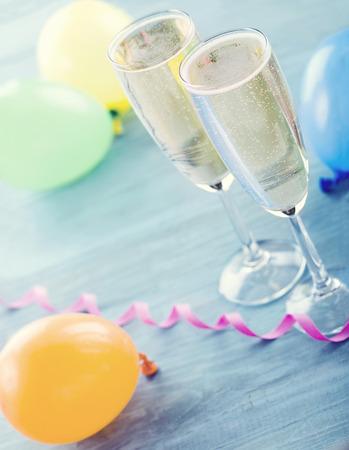 Twee glazen champagne en kleurrijke ballonnen op blauwe houten achtergrond - een partij concept Stockfoto