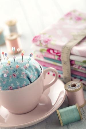 Green handgemaakte bloemen speldenkussen in een roze kop met oude spoelen van draad, het naaien concept achtergrond