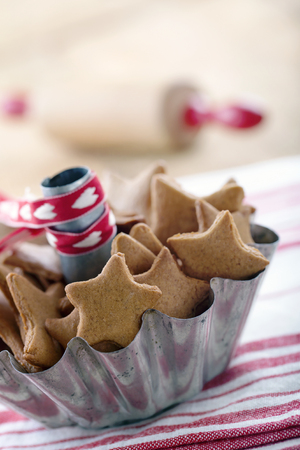 Homemade Christmas gingerbread cookies in a rustic metal cup on red vintage background Banco de Imagens