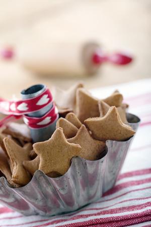 Zelfgemaakte Kerst pepernoten in een rustieke metalen kop op rode vintage achtergrond Stockfoto
