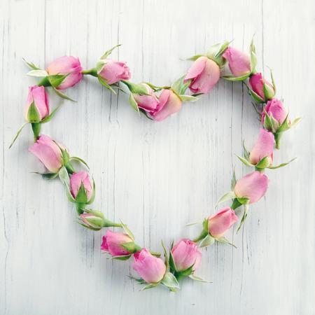 Hart van roze rozen op witte houten achtergrond