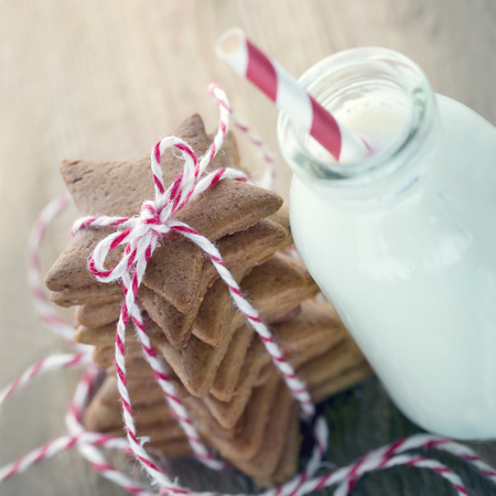 Homemade Christmas gingerbread cookies with a bottle of milk on wooden vintage background Banco de Imagens