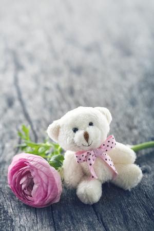 Zachte pluche teddybeer met een roze ranunculus bloem op houten uitstekende achtergrond voor een verjaardag of Valentines viering