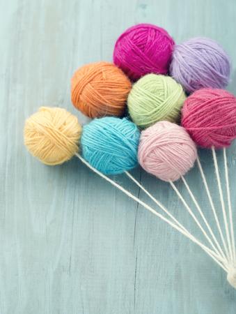 Ballen van de draad als een groep van kleurrijke ballonnen op lichte blauwe houten uitstekende achtergrond