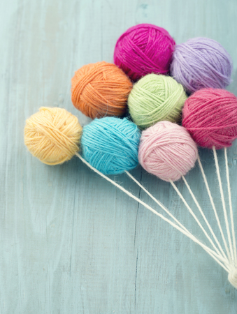 Balls of thread as a group of colorful balloons on light blue wooden vintage background