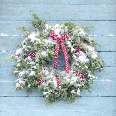 Christmas wreath on wooden vintage blue background and snowflakes