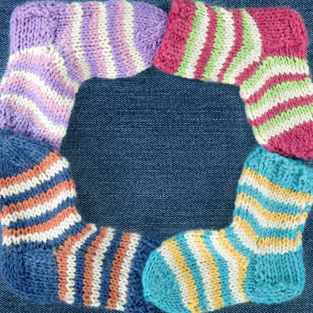 Small colorful woolen socks on blue denim background - knitting crafts concept