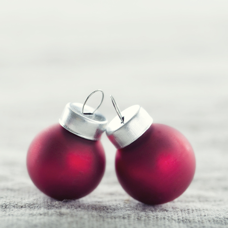 Simple small red Christmas baubles on rustic linen background with vintage editing