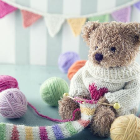 Teddybeer in een wollen trui breien een gestreepte sjaal met kleurrijke ballen van garen Stockfoto