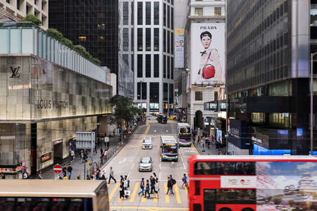Hong Kong, China- March 04 2019: Pedestrians cross Pedder Street by a Louis Vuitton store in Central. The tourism industry is an important part of the economy of Hong Kong.