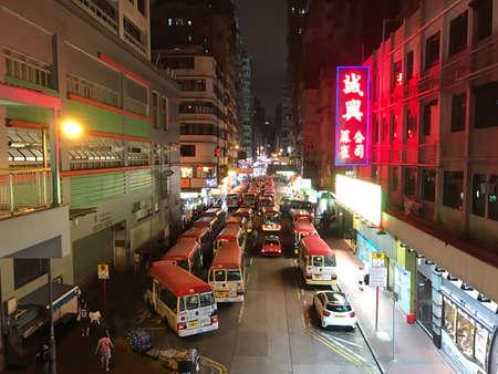 Mongkok Hong Kong, China - 19 May 2019: Red Minibuses lining up, waiting for passengers at a busy station in Mongkok, Hong Kong at night. Redactioneel